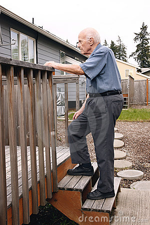 Senior walks up wooden deck steps outside