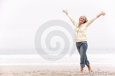 Senior Woman With Arms Outstretched On Beach