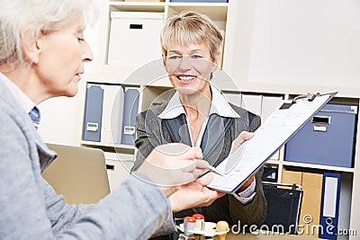 Senior woman in bank signing