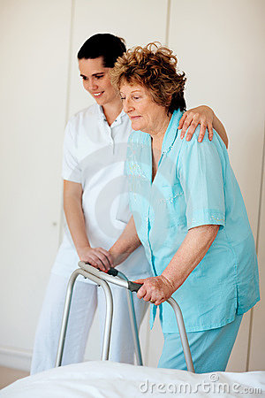 Senior woman being helped by a nurse to walk