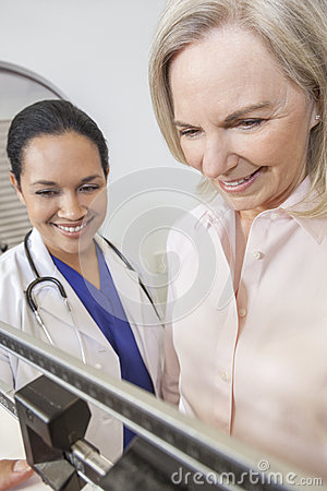 Senior Woman Being Weighed by Doctor Nutritionist