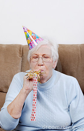 Senior Woman With Birthday Hat Blowing Noise Maker
