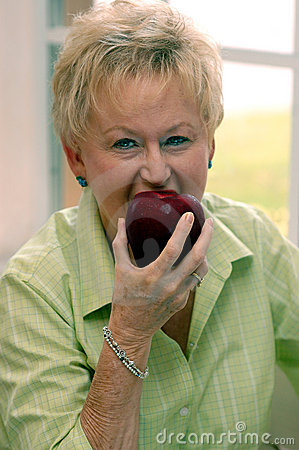 Senior woman biting apple