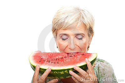 Senior woman biting watermelon