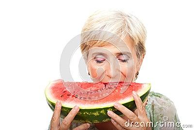 Senior woman biting watermelon