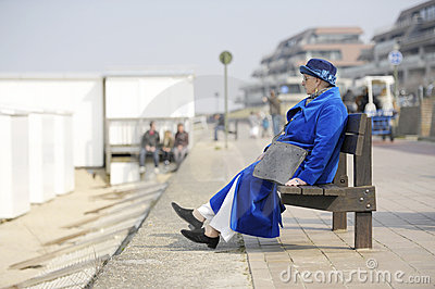 Senior woman in blue coat & hat on a bench