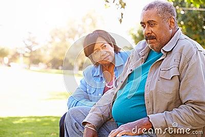 Senior Woman Comforting Unhappy Senior Husband Outdoors