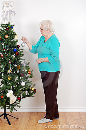 Senior woman decorating her christmas tree