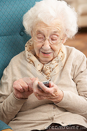 Senior Woman Dialling Number On Mobile Phone