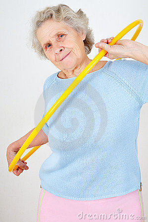 Senior woman doing gymnastic with hula-hoop
