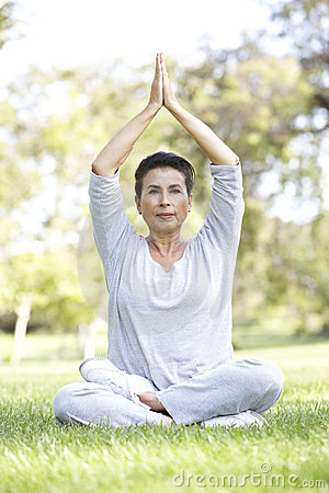 Senior Woman Doing Yoga In Park