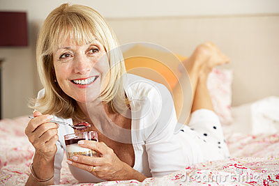 Senior Woman Eating Dessert In Bed