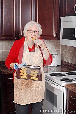 Senior woman eating fresh cookie