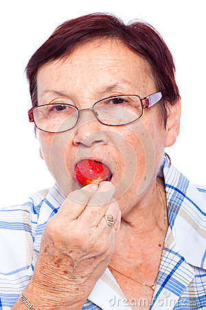 Senior woman eating strawberry