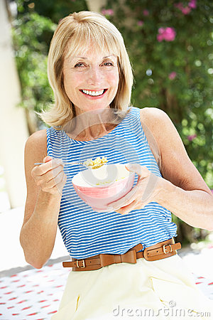 Senior Woman Enjoying Bowl Of Breakfast Cereal