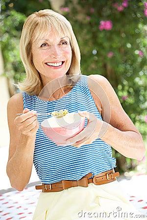 Senior Woman Enjoying Bowl Of Breakfast Cereal