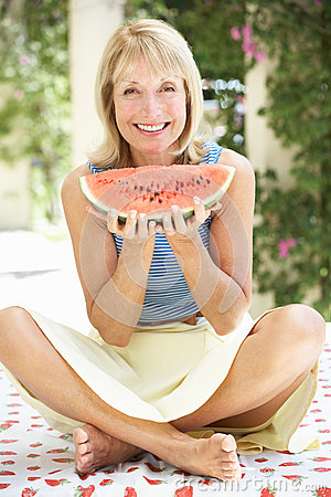 Senior Woman Enjoying Slice Of Water Melon