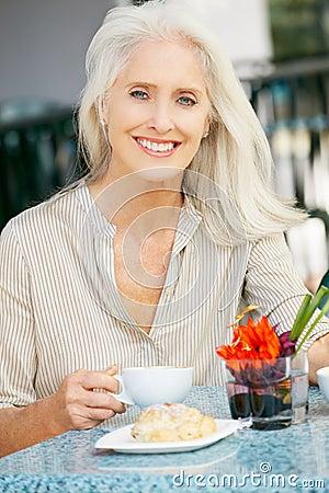 Senior Woman Enjoying Snack At Outdoor Cafe