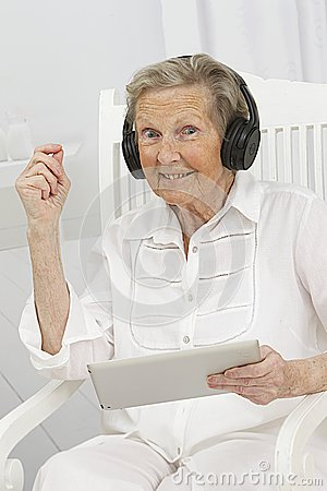 Senior woman enjoying some music videos on her tablet device