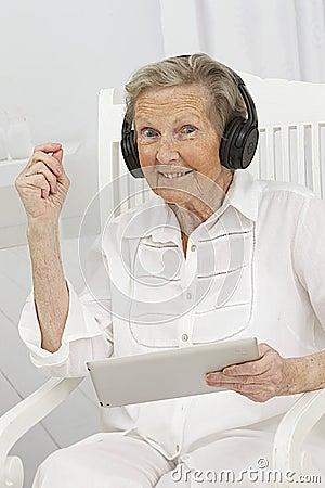 Senior woman enjoying some music videos on her tablet device