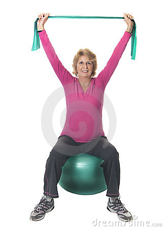 Senior woman exercising with ball and band