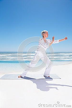 Senior woman exercising at the beach