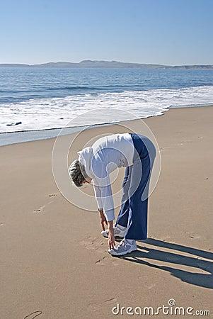 Senior woman exercising on beautiful beach