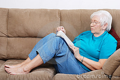 Senior woman falling a sleep while reading book