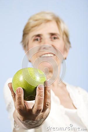 Senior woman giving an apple