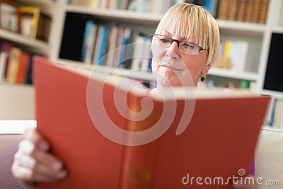 Senior woman with glasses reading book at home