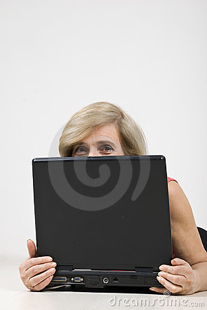 Senior woman hiding behind laptop