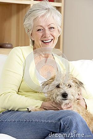 Free Senior Woman Holding Dog On Sofa Stock Images - 12407184