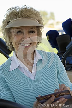 Senior woman holding golf score card