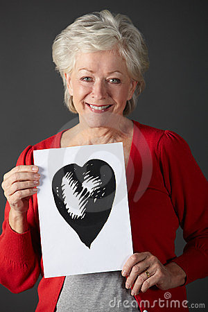 Senior woman holding ink drawing of heart