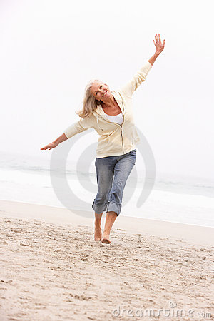Senior Woman On Holiday Running Along Winter Beach
