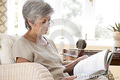 Senior woman at home reading book