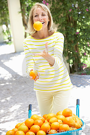 Senior Woman Juggling Oranges By Wheelbarrow