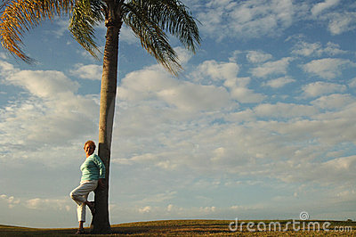Senior woman leaning against palm tree