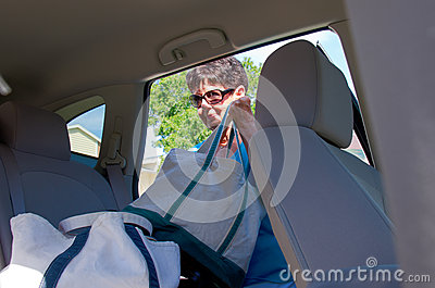 Senior woman loading bags into a vehicle