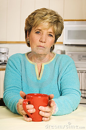 Senior woman, looking unhappy, holds a coffee mug
