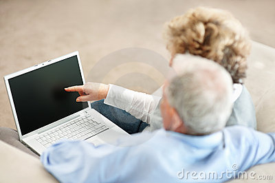 Senior woman with a mature man pointing at laptop