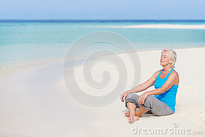 Senior Woman Meditating On Beautiful Beach