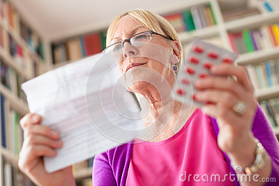 Senior woman with pills and prescription