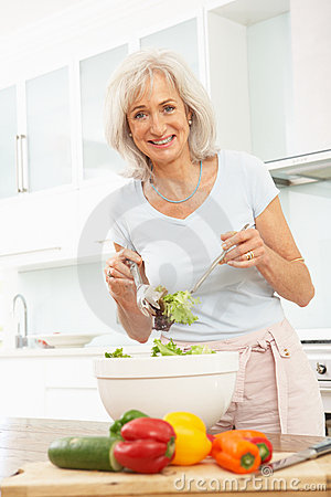 Senior Woman Preparing Salad In Modern Kitchen
