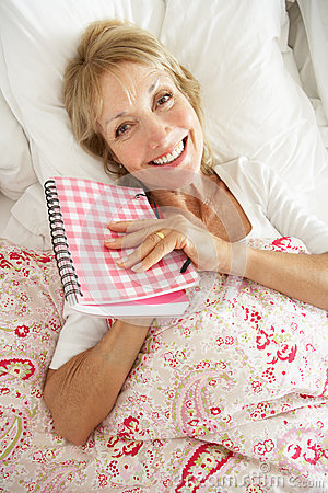 Senior Woman Relaxing In Bed Reading Diary