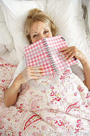 Senior Woman Relaxing In Bed Reading Diary Stock Photography - Image: 26616332