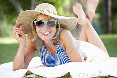 Senior Woman Relaxing In Summer Garden