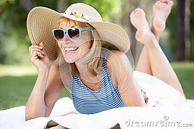 Senior Woman Relaxing In Summer Garden