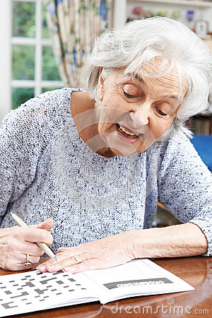 Free Senior Woman Relaxing With Crossword Puzzle At Home Royalty Free Stock Photos - 55692128