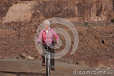 Senior Woman Riding Bike Through the Desert